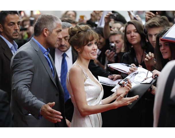 "Actress Angelina Jolie signs autographs for fans as she arrives for France's premiere of her movie ""Salt"" in Paris"